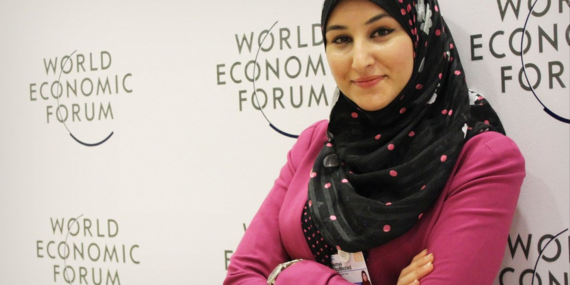 Woman in front of World Economic Forum poster