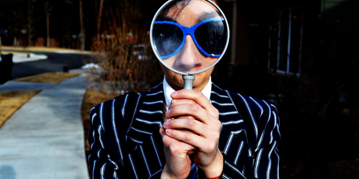 person holding a magnifying glass in front of their face