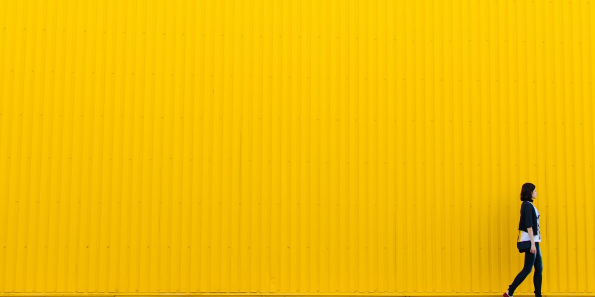Woman walking by yellow wall