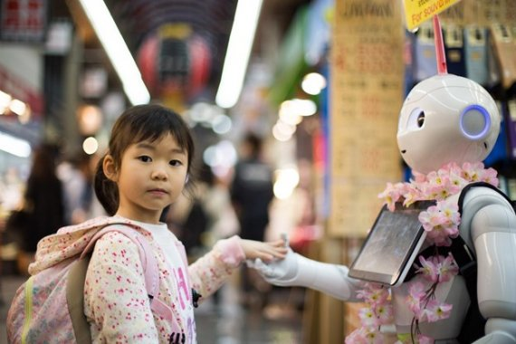 young girl touching a robot