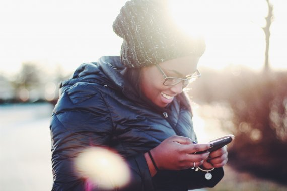 woman looking happily at her phone